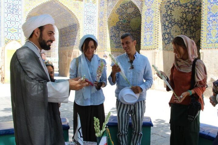 iranian cleric offering flowers to western tourists things to know before traveling to iran 3